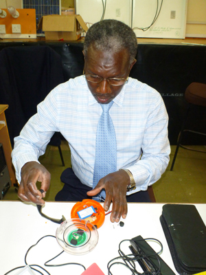 One of the Senegalese lighting quality experts practically examines a solar lantern at the University of Nairobi during a recent training.