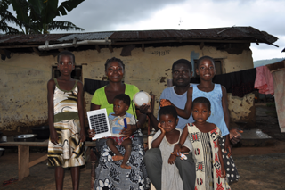 The Danquah family outside their home in Nimforkrom, Ghana showing off a solar panel and a versatile lamp that has lit up their nights and changed their lives ©Lighting Africa