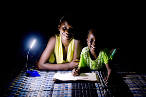 Children read a school book with a solar lamp in Dakar, Senegal.© Bruno Déméocq/Lighting Africa