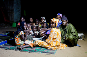 Better lights for better lives: here, a group of people eating under the light of a solar lamp, Senegal. © Bruno Déméocq/Lighting Africa/2012.