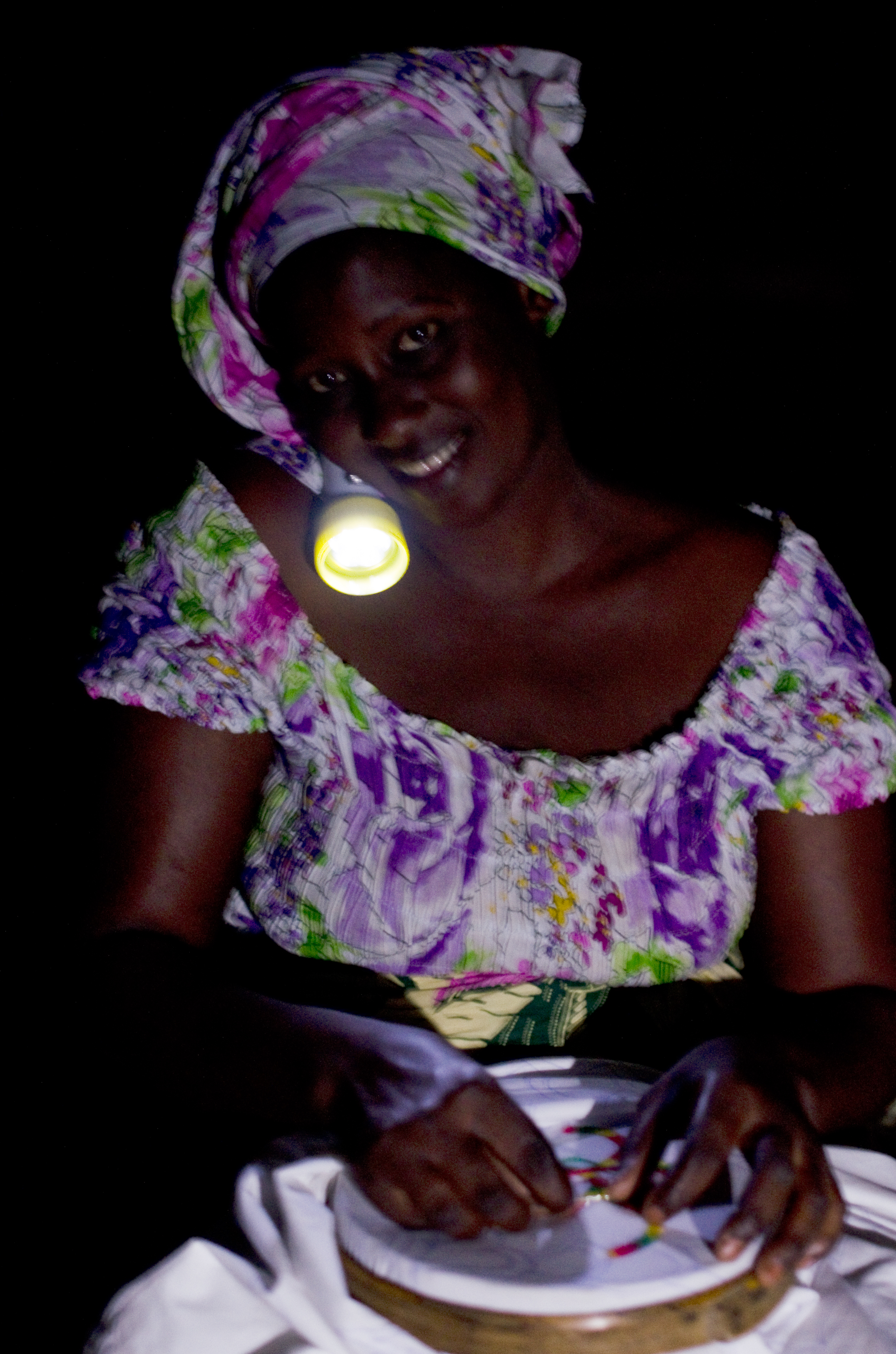 A woman in Dakar does some evening beadwork with one of the off-grid lights that are lighting the nights across Africa © Bruno Demeocq/Lighting Africa