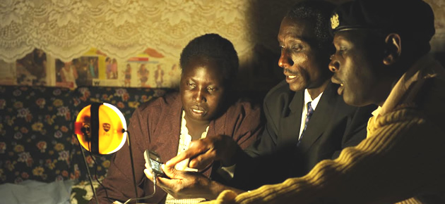 Chief Paul Tirop (centre) demonstrates how modern solar lamps also charge mobile phones