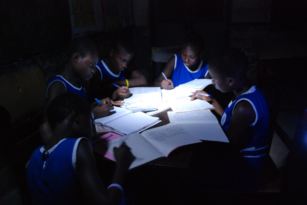 Boys studying with a solar lamp