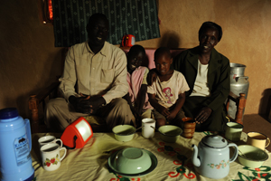 Mrs Cheruyiot with her husband and children at their home, their S250 lamp charging behind them © Lighting Africa