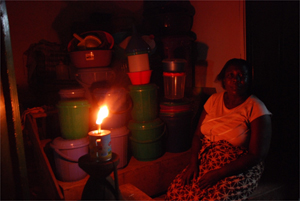 A woman at her store, which is lit by the open-wick kerosene lamp; The new Kenya Government initiative is expected to put to an end the use of such hazardous and polluting energy sources, and make clean energy products widely available in Kenya © Katia Theriault